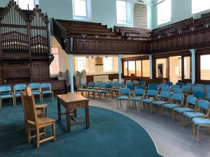Lightweight wooden stacking chairs for Taunton united reformed church, and in the background lightweight high stacking sled base or skid base upholstered chairs